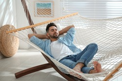 Young man relaxing in hammock at home