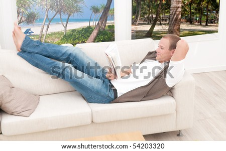 Young man relaxing in his beach house - stock photo