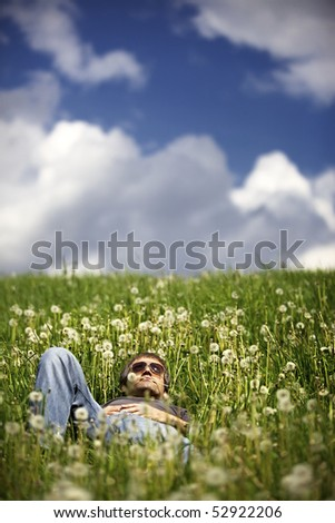 Young man relaxing in meadow with blow ball flower in mouth and beautiful sky in the background.