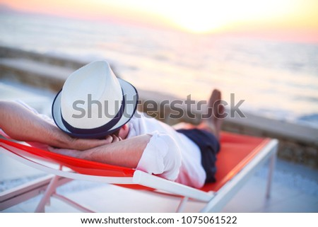 Young man relaxing on the beach back view. Summer vacation. Relax concept #1075061522