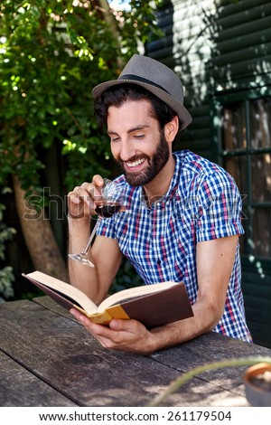young man relaxing outdoors reading literature novel story book with glass red wine at home