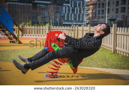 Young man reliving his childhood plying in a children's playground riding on a colorful red spring seat with a happy smile in an urban park