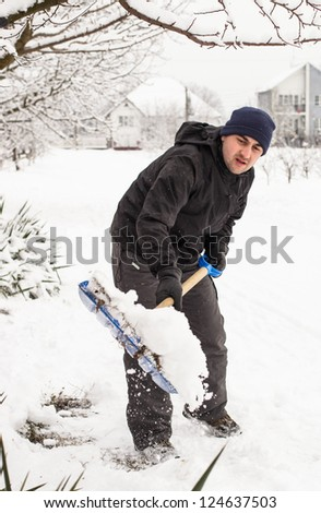 Young man remove snow near the suburban house