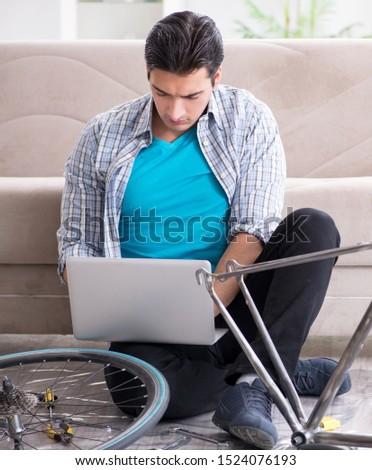 Young man repairing bicycle at home