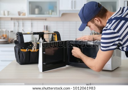 Young man repairing microwave oven in kitchen #1012061983