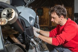 Young man repairing or preparing a motorbike for a new season after winter time, basic motorcycle maintenance