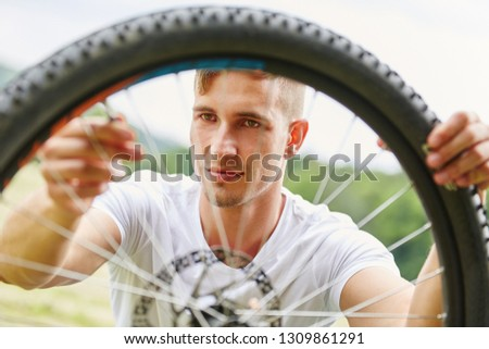 Young man repairs tire hoop of mountainbike after breakdown #1309861291