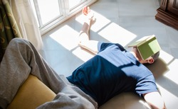 Young man resting on the floor whit a book on his face while enjoying the sun coming through the window. Concept of stay at home, freedom, boredom...