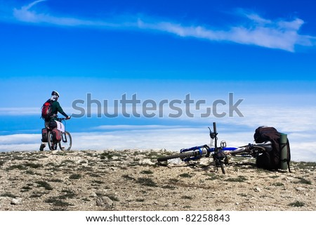 Young man riding a bike over the precipice in the mountains