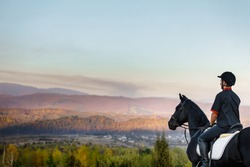 young man riding a horse in mountains near lake and old mill. equestrian sport concept. man's equitation on black horse. professional male jockey. vacation on horse farm. vacation with horses. hobby