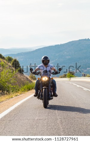 Young man riding a motorcycle on road in mountains in sunny day.