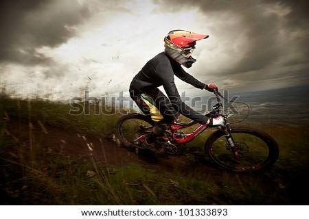 Young man riding a mountain bike downhill style - stock photo