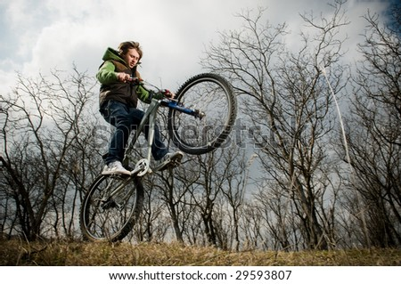 Young man riding bike, low angle view, motion blur