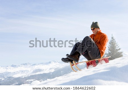 Young man riding down a snowy slope on a sled and smiling on a bright, sunny day Foto stock ©