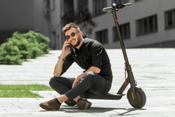 Young man riding electric scooter in urban background