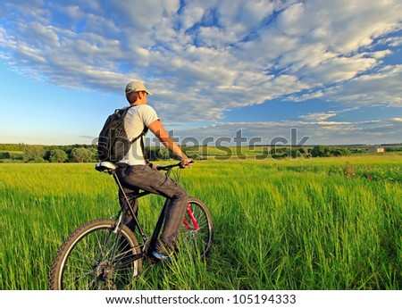 Young man riding on a bicycle on green meadow with a backpack