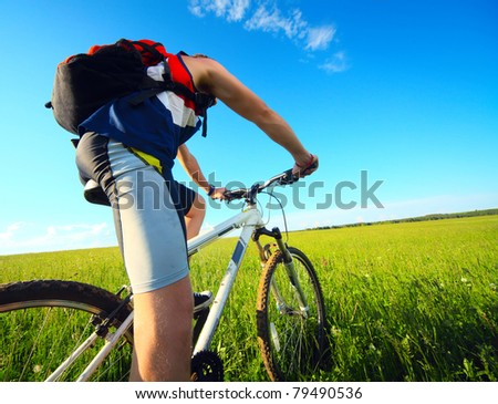 Young man riding on a bicycle on green meadow with a red backpack