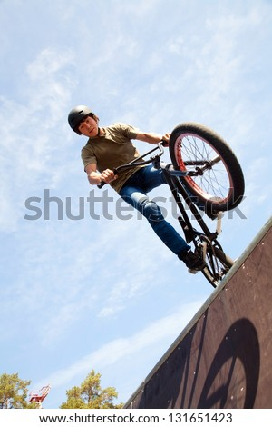 Young man  riding on a BMX bicycle on a ramp over blue sky background