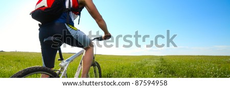 Young man riding on bicycle on a green meadow with red backpack