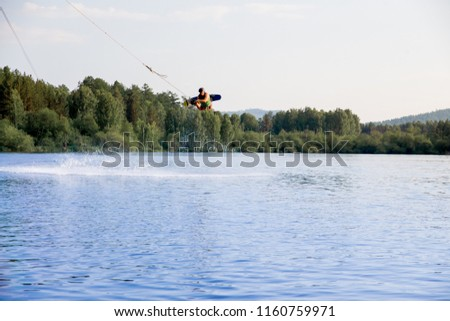 Young man riding wakeboard on a lake #1160759971