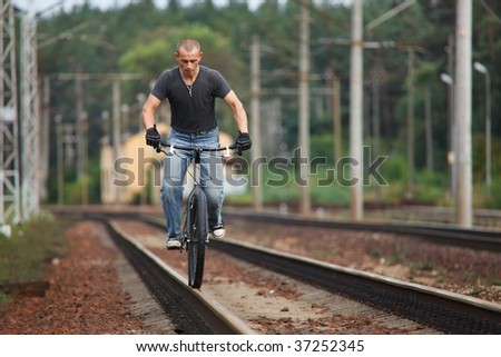 Young man riding with bicycle on railways rail. Low angle view with selected lighting.