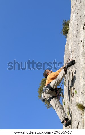 young man rock climbing in french