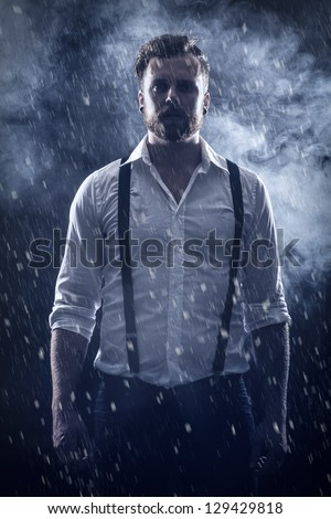 Young man / rocker with ear rings standing in the snow with smoke in the background .