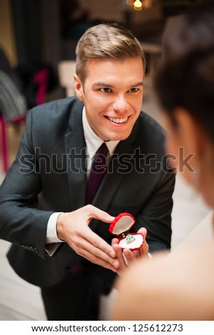 Young man romantically proposing to girlfriend and offering engagement ring