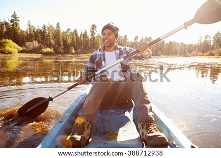 Young Man Rowing Kayak On Lake