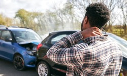 Young man rubbing neck in pain from whiplash injury standing by damaged car after traffic accident