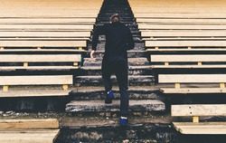 Young man runner in sport clothes running climbing stairs in the stadium