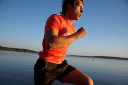 Young man running along the seashore at sunset.