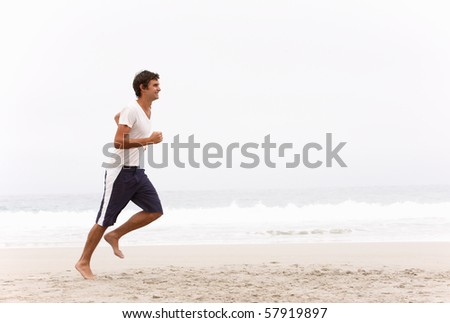 Young Man Running Along Winter Beach