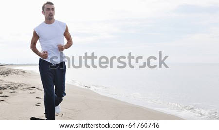 young man running and jogging at early morning on beach