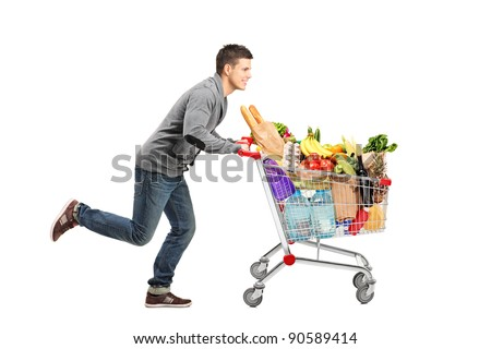 Young man running and pushing a shopping cart full with food isolated on white background