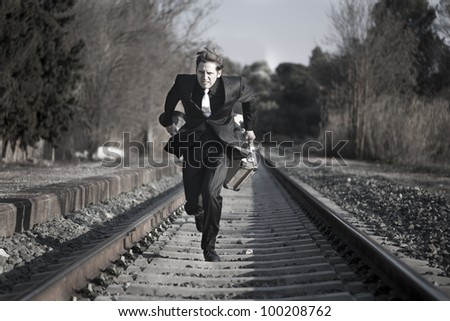 Young man running down the railway tracks with luggage and suit