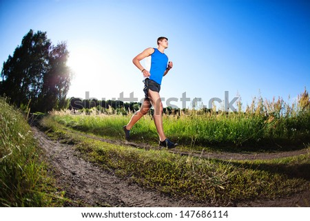 Young man running in countryside. Healthy lifestyle - stock photo