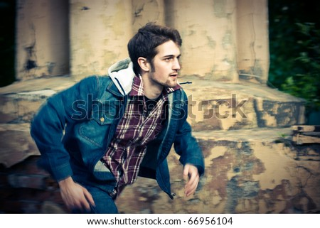 Young man running in front of the ruined wall. Captured motion with panning, motion blur. - stock photo