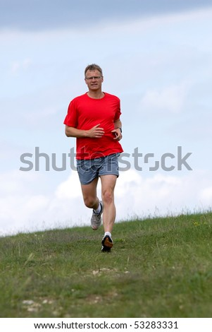 Young man running on a green field