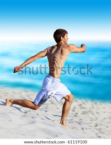 Young man running on beach.