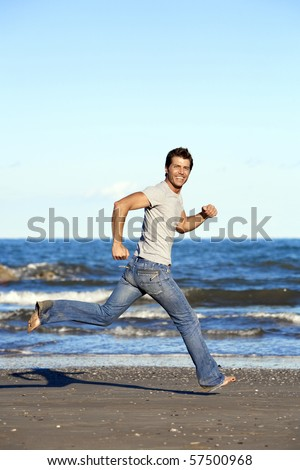 Young man running on beach barefoot in casual clothing