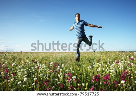 Young man running on meadow with pink flowers and green grass on a blue sky