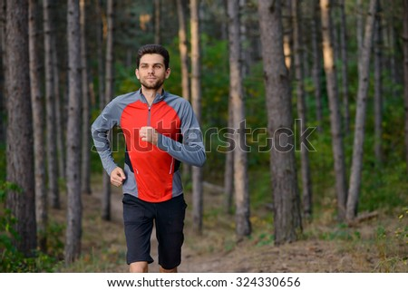Young Man Running on the Trail in the Wild Pine Forest. Active Lifestyle Concept