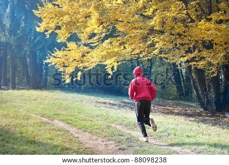young man running  the autumn forest