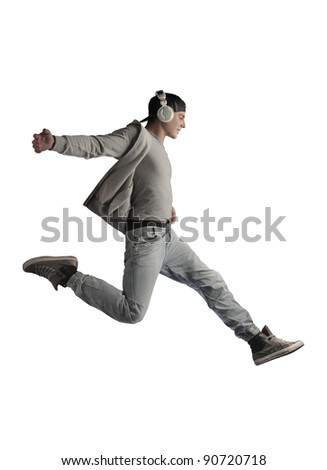 Young man running while listening to music stock photo