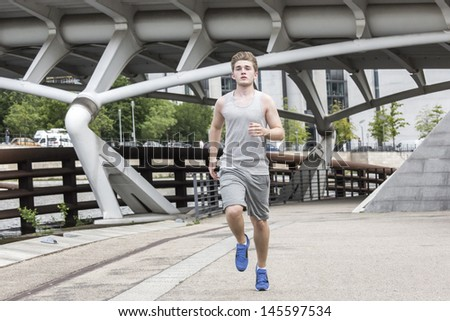 Young man runs at the town center waters