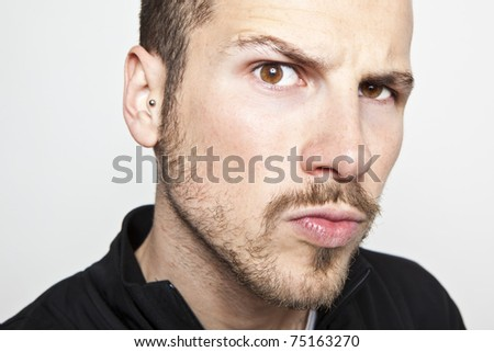 young man's face, intense look - stock photo