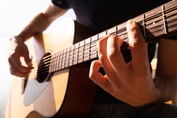 Young man's hands playing acoustic guitar, close up