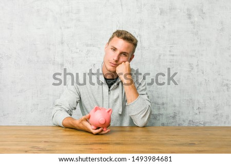 Young man saving money with a piggy bank who feels sad and pensive, looking at copy space.