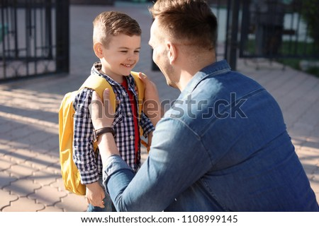 Young man saying goodbye to his little child near school #1108999145